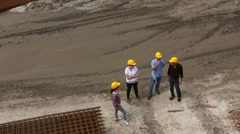 Team of managers in yellow helmets is talking on construction site. Stock Footage