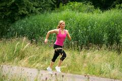 Healthy woman jogging in the park on a summer day - stock photo