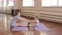 Pregnant woman with her first kid daughter doing gymnastics Arkistovideo