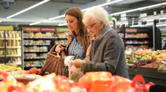 Elderly woman with young woman at the grocery store - stock footage