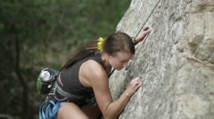Rock climbing woman, with dreads, chalking her fingers. - stock footage