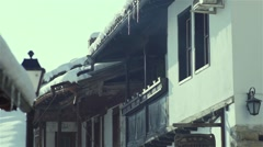 Snow melts in slow motion from an old wooden house Stock Footage