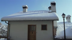 Small house with a snow roof and chimney running Stock Footage