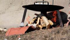 Burning wood under a metal disc on that fry meat cuts  Stock Footage