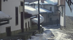 Man and cat walk in the old stone street with old houses with snowy roofs Stock Footage