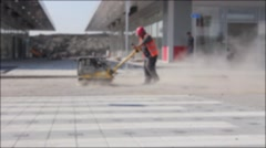 Blurred view on worker who controls plate compactor. Stock Footage