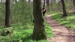 Girl playing hide-and-seek. It is hidden behind the tree and they head out  Stock Footage