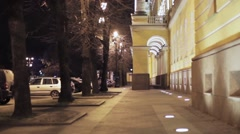 View of street with yellow buiding and trees in night city. Illumination lights Stock Footage