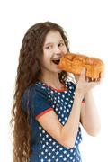 Schoolgirl biting off piece of bread Stock Photos