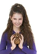 smiling schoolgirl with pine cones - stock photo
