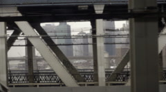 Gritty Lower Manhattan through bridge steel beams moving subway train NYC Stock Footage