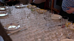 Mistress puts glasses and wine glasses on a festive table. 4K. - stock footage
