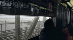B train Brighton Beach with man coat hat looking out window East River Brooklyn Stock Footage