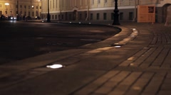 View of street with yellow buildings in night city. Camera on ground Stock Footage