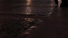 View of asphalt in night city. Man and woman feets go on road. Camera on ground Stock Footage