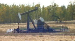 Rack focus of pump jacks working in a field for oil and gas industry. Stock Footage