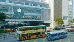 Urban traffic passing an enormous Apple store in Hong Kong. UltraHD video - stock footage