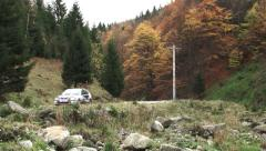 Rally place on a mountain road. A car passing on the road. Rally takes place Stock Footage