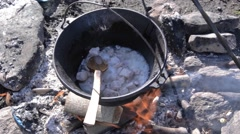 Stew made ​​traditional cauldron on wood fire. A man mixed meat in pot  Stock Footage