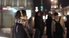 Young girl stay in night street and listen music in yellow earphones Stock Footage