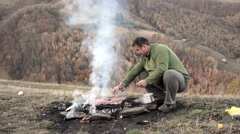 Stock Video Footage of Steak and other meat on barbeque grill with flames. A man puts the meat