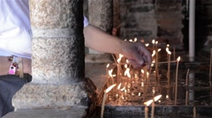 Women who are on a pilgrimage to a church lit candles in memory of loved ones  Stock Footage
