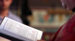 The priest officiating at the marriage service, taking Bible in hand and read  - stock footage