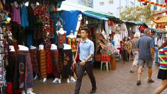 Boy playing with a pinwheel as tourists browse several roadside shopping stal Stock Footage