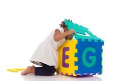 Little African American baby girl playing with construction games isolated on Stock Photos