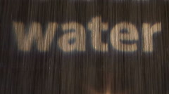 Water word letters projection on waterfall rain Stock Footage