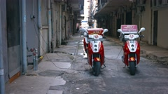 Kentucky Fried Chicken's electric delivery scooters, charging in an alley Stock Footage