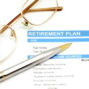 retirement plan document with pen and glasses - stock photo