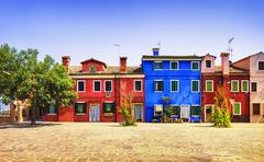 Venice landmark, Burano island square, tree and colorful houses, Italy Stock Photos