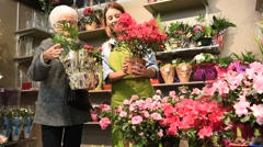 Senior woman in flower shop with florist - stock footage