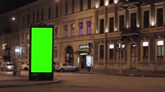 Night city street. Buildings, green advert screen. Flashing traffic light. Empty - stock footage