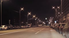 View of night road with flashlights and parked cars in city. No traffic, people Stock Footage
