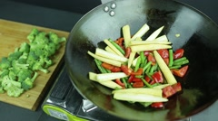 Man preparing curry vegetables on the wok pan Stock Footage