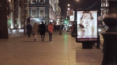 View of night street in city with walking people and advert bilboard - stock footage
