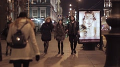 View of night street in city with walking people and advert screen - stock footage