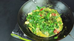 man preparing curry vegetables with cocount milk on the wok pan - stock footage