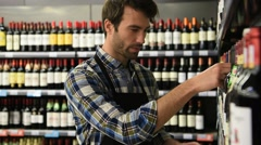 Wine specialist putting bottle up in winery section of supermarket - stock footage