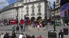 Stock Video Footage of 4K Pan right follow red bus transportation London Piccadilly Circus emblem icon