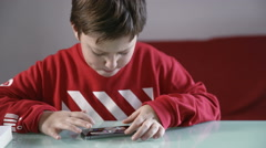 child sat at home and playing with a videogame on smartphone - stock footage
