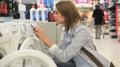 Woman comparing washing machine details with smartphone - stock footage