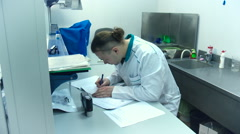 Man in a white coat makes notes about his research in the laboratory Stock Footage