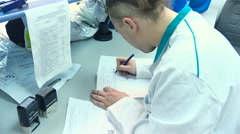 Man in a white coat makes notes about his research by hand in the laboratory - stock footage