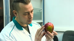 Man in a white coat makes the examination of a mango fruit in the laboratory - stock footage