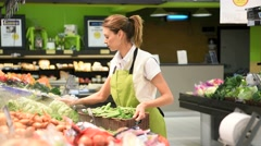 Supermarket employee putting vegetables in shelves Stock Footage