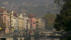 People walking on Cumurija Bridge and Obala Kulina bana street in Sarajevo Stock Footage