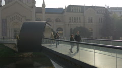 The Academy of Fine Arts and people walking on Festina Lente bridge in Sarajevo Stock Footage